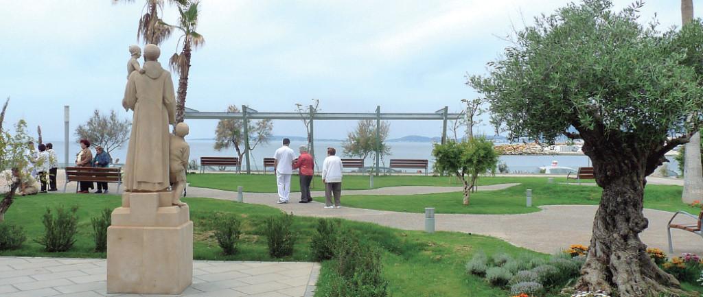 Unos pacientes pasean con sus cuidadores y familiares por los jardines de Sant Joan de Déu.